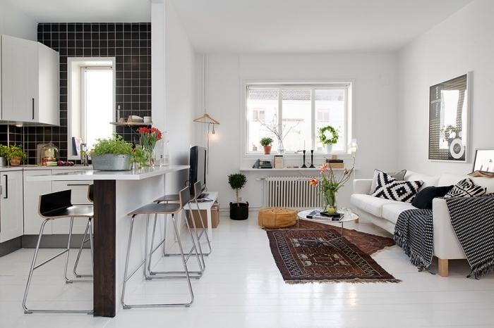 astuce et idée aménagement studio aux murs blancs avec petite cuisine d'angle au carrelage partiel en noir et armoires blanches