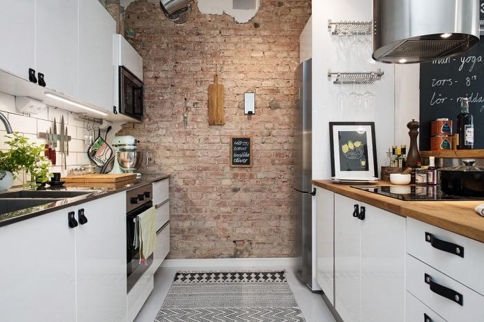 déco industriel dans une petite cuisine blanche avec jolie décoration de pan de mur en briques rouges et meubles blancs