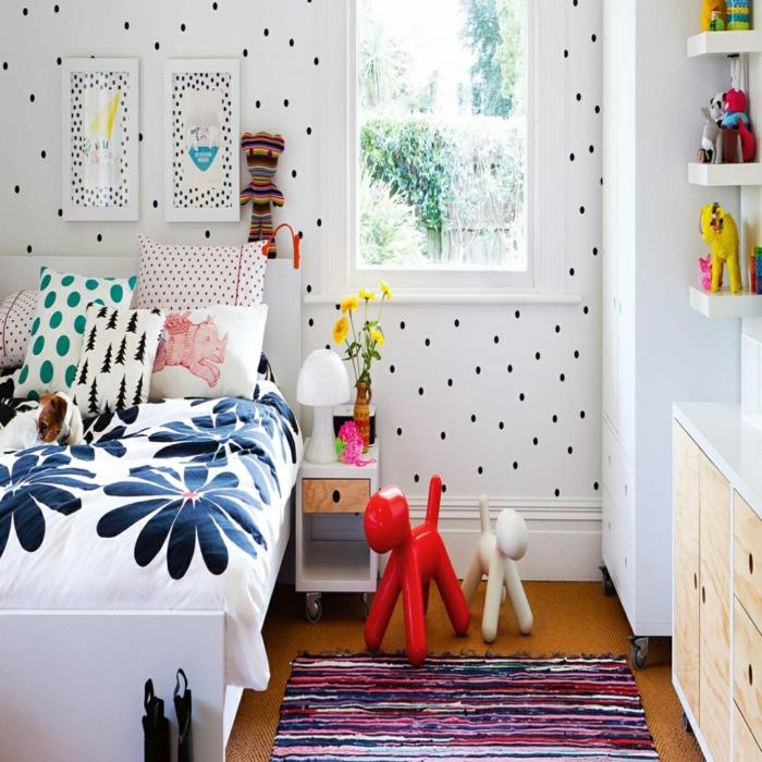 deco mural papier peint blanc avec des petits pois noirs, tapis en style ethno en bleu et rose, lit avec couverture en blanc et bleu aux motifs fleuris, meuble en blanc avec des effets boisés en PVC