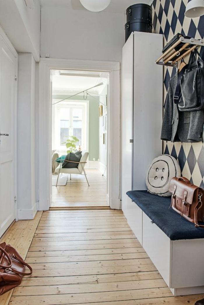 entrée aux murs blancs avec un mur habillé en papier peint en ivoire et bleu marine, motifs losanges, decoration murale design, idee deco mur, décoration murale chambre, meuble rangement chaussures en bleu marine et blanc