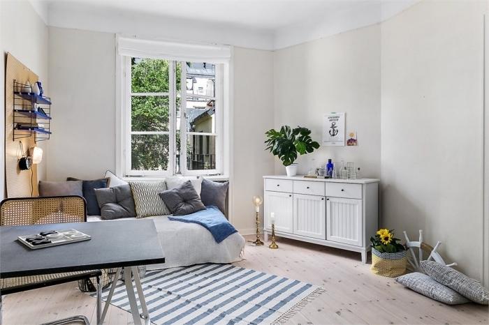 ambiance cozy dans un petit studio étudiant aménagé avec lit couvert de coussins et table à manger ou bureau noir