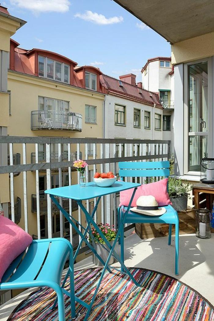 deux chaises et une table pliables en métal bleu pastel, tapis rond en style ethnique, garde-corps en métal gris, idee deco terrasse, decoration terrasse exterieur