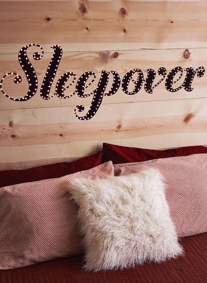 tete de lit en planches de bois avec des lumières intégrées, linge de lit rouge, coussins décoratifs originaux