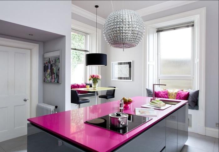 une cuisine gris laqué qui fait très chic avec son îlot central fonctionnel équipé d'un point de cuissin, évier encastré et son comptoir rose fuchsia laqué