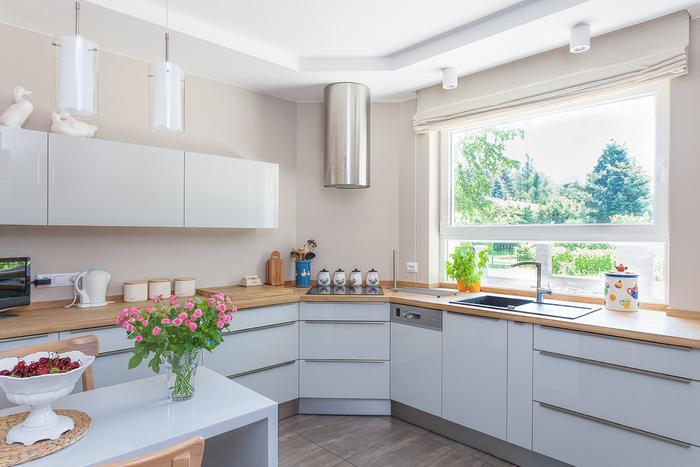 ambiance chaleureuse grâce à l'association d'une cuisine gris laqué et de la couleur beige aux murs, ainsi qu'au comptoir en bois clair