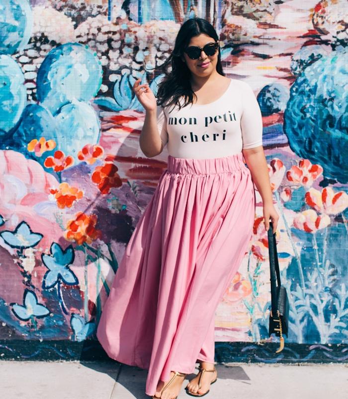 jupe grande taille couleur rose pale, tee shirt blanc avec lettres noires, cheveux chatain foncé, sandales femme, lunettes de soleil, sac à main noir tendance