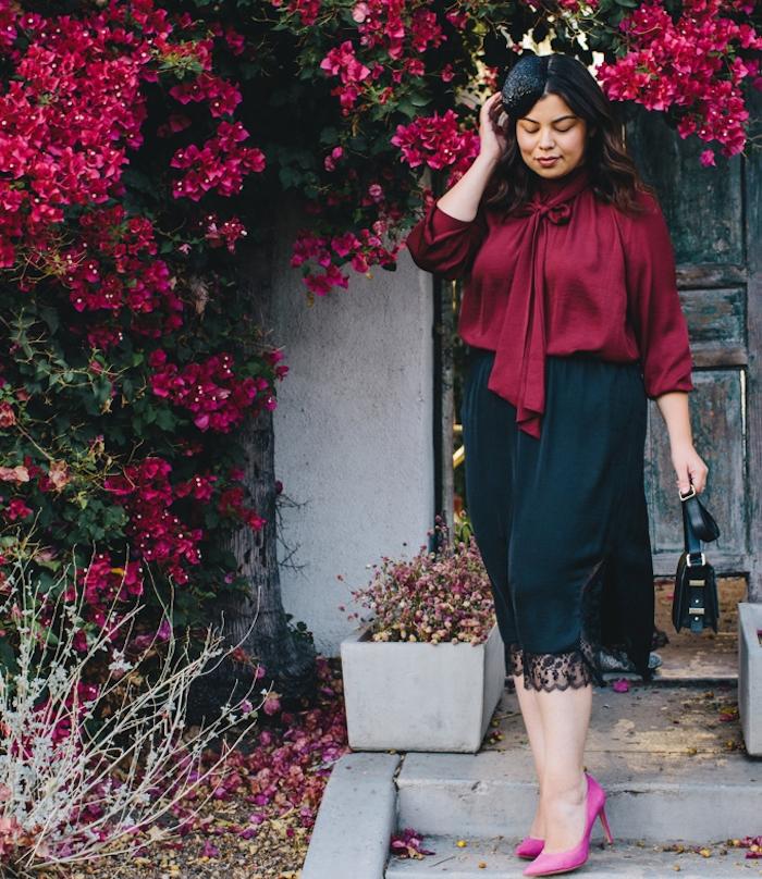 tenue de ceremonie femme, chemise bordeaux, jupe noire à ourlet dentelle, chaussures mauve, bonnet femme noir, fond fleuri