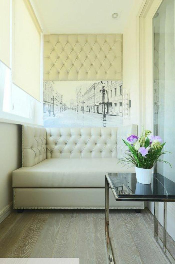 idee deco terrasse en style élégant et glamour, canapé en simili cuir couleur ivoire, table avec plan en verre trempé noir, sol en carrelage imitation bois gris