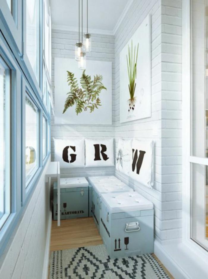 trois tabourets réalisés avec des caissons peints en bleu pastel avec des coussins carrés blancs, idee deco terrasse, idee amenagement terrasse, tapis rectangulaire en noir et blanc, deux panneaux muraux avec des images plantes vertes de jardin, murs en briques blanches