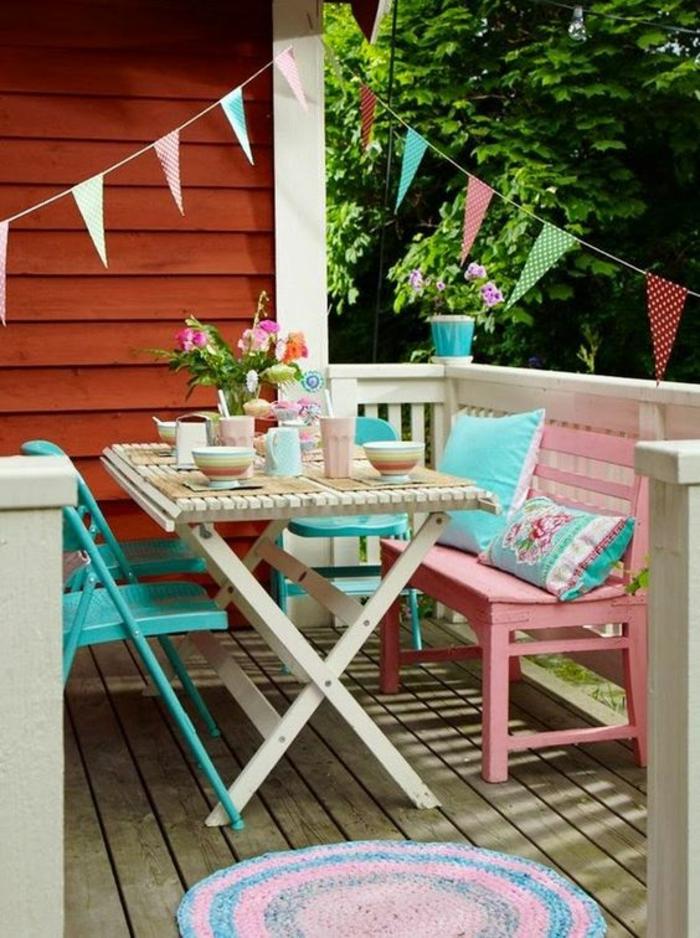 deux chaises pliables en métal bleu pastel. un banc en bois rose avec deux coussins en turquoise et rose, déco jardin récup, table pliable en bois blanc avec couverture jaune, petit tapis rond en rose et bleu pastel