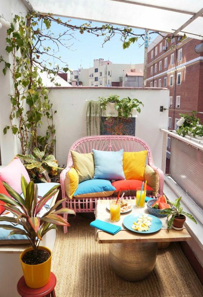 aménagement terrasse appartement, canapé deux places en rotin rose, banc avec matelas bleu et coussins rose et orange, pot plante en orange, table bronze