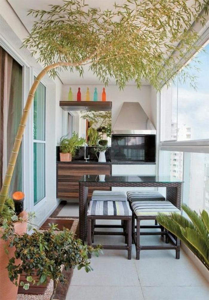 idee amenagement terrasse avec four et barbecue, arbre de bambou, table en bois marron, quatre tabourets avec des pieds bois marron et tissu rayures horizontales et verticales bleues et grises