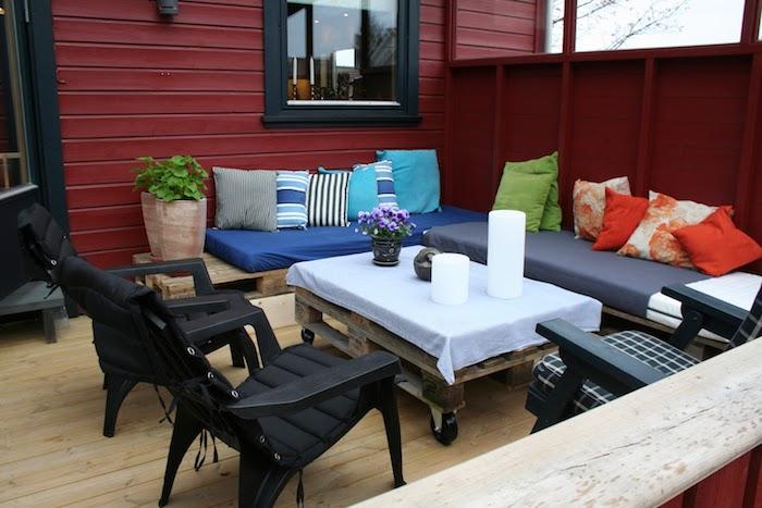 exemple de terrasse couverte avec une table palette basse et canapé d angle en palettes, chaises noires, multitude de coussins décoratifs colorés