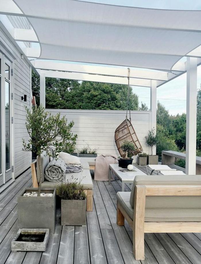 idee amenagement terrasse, idee deco terrasse en style nordique, meubles en bois clair avec des coussins réséda, sol recouvert de bois en couleur grise, pots de plantes carrés, voilages blancs et pergola au-dessus des meubles