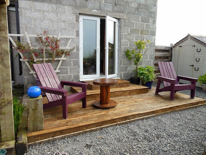 terrasse en bois avec des chaises longues mauves et une table en touret basse, deco de végétation