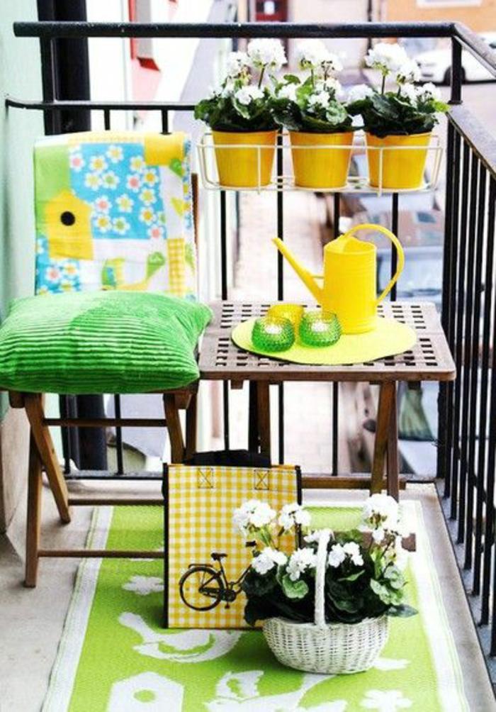 espace aménagé en couleurs vibrantes, idée déco terrasse en vert et jaune, trois pots jaunes sur le garde-corps, tapis en vert réséda et blanc avec des motifs oiseaux, coussin vert pomme sur une chaise pliante en bois marron