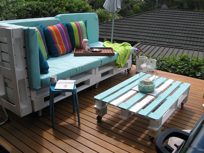 coussin salon de jardin palette bleu sur un canape palette blanchi, table basse avec palette à roulettes, terrasse bois