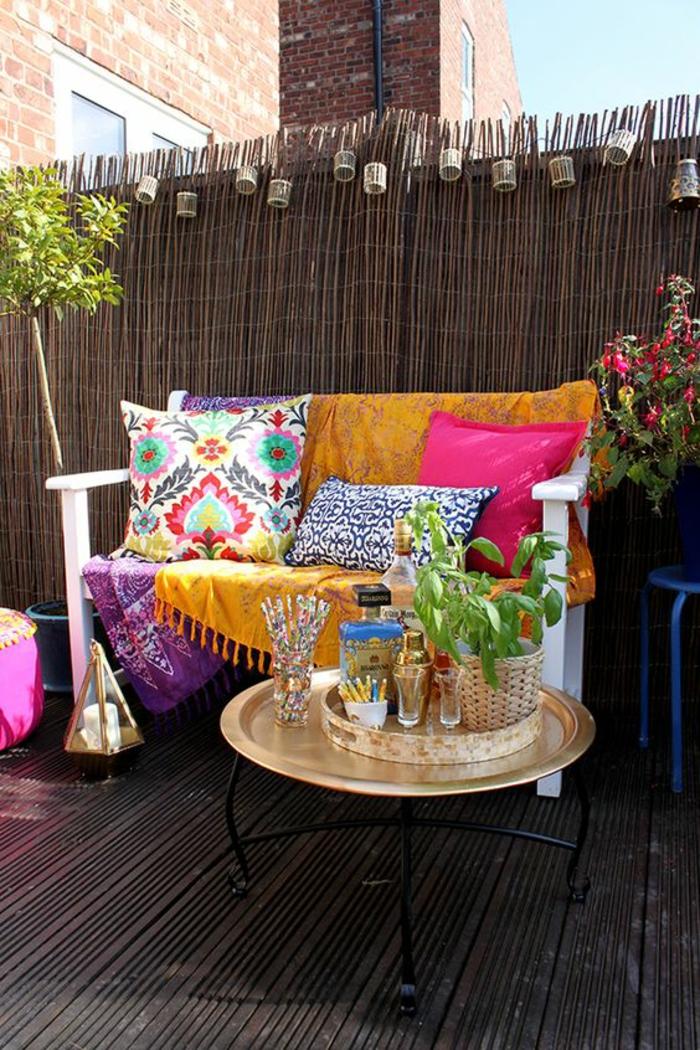 aménagement terrasse en style marocain, idée déco terrasse, sol recouvert de bois marron, banc avec dossier deux places en bois peint en blanc, recouvert de coussins en couleurs vives, couverture orange avec des franges, table basse ronde en métal doré marocaine, plan brillant au soleil