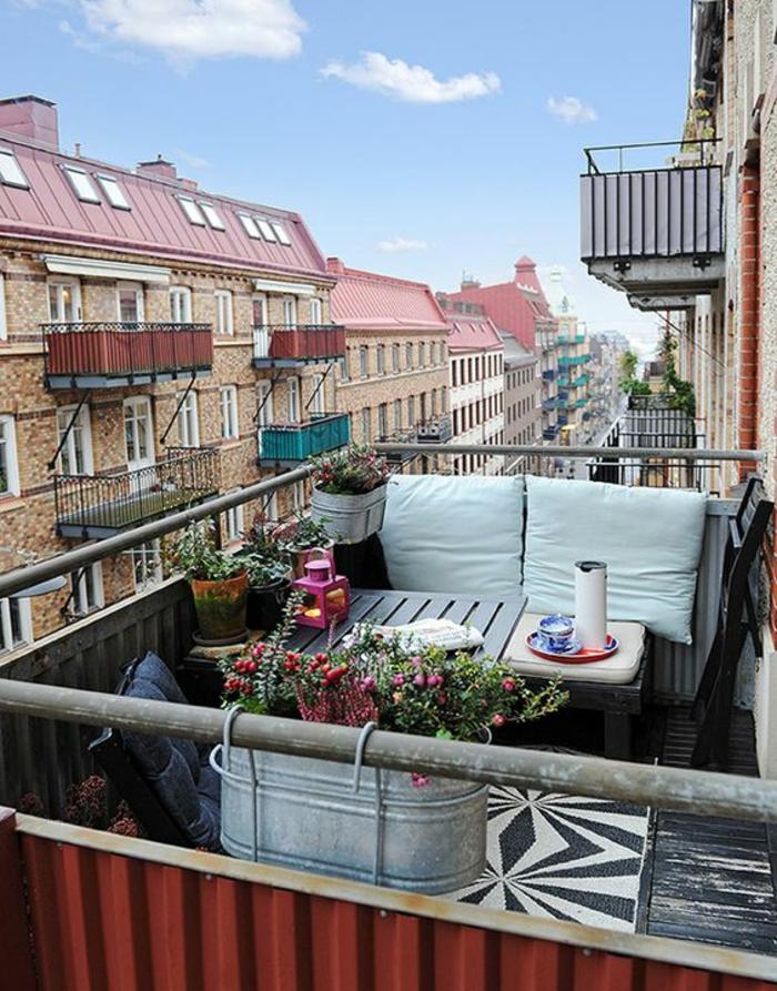 amenagement petite terrasse, aménagement terrasse appartement, ville suédoise, balcon fleuri, avec des porte-plantes en métal couleur argent, tapis motifs graphiques en noir et blanc, sol recouvert de bois peint en noir usé