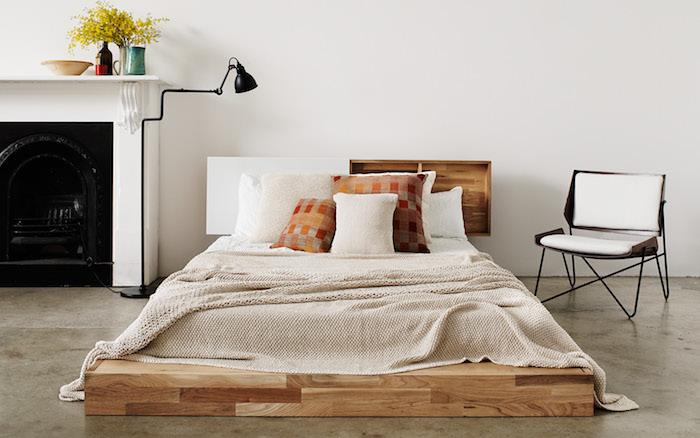 idee tete de lit originale en meuble bois, lit matelas sur un plateau en bois, sol gris avec cheminée blanche originale