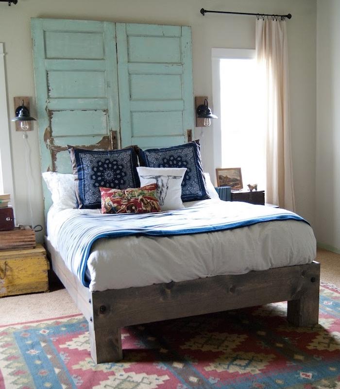 comment faire une tete de lit en portes bois recyclés bleues, linge de lit bleu et blanc sur un lit bois, tapis oriental coloré, deco chambre vintage chic