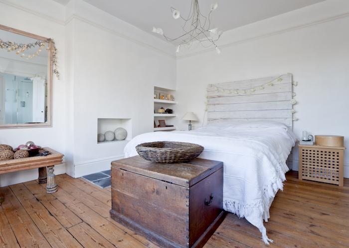 tete de lit palette de bois blanchi, décoration guirlande, bout de lit en coffre bois, parquet bois, mur avec niches murales