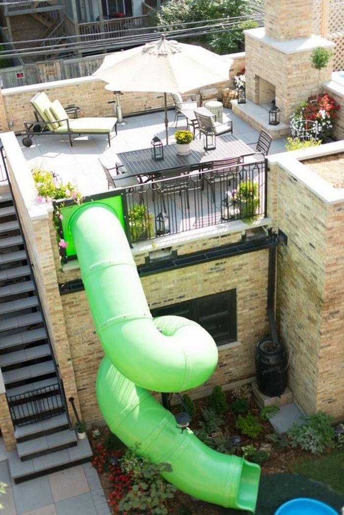 toboggan extrême en plastique verte qui part de la terrasse et descend au niveau inférieur de la maison, decoration jardin terrasse