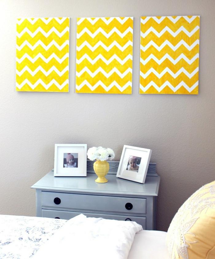 deco mural, décoration murale chambre, trois panneaux en jaune et blanc aux motifs graphiques, meuble de rangement en bleu pastel avec des poignées rondes noires, lit matrimonial avec couverture blanc et bleu et coussins jaunes