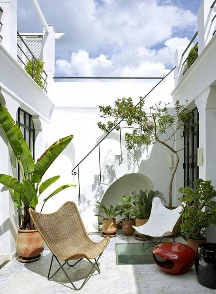 meubles de jardin design, un fauteuil en rotin tressé beige avec du métal noir, fauteuil en simili cuir blanc et en métal noir, amenagement petite terrasse, idee deco terrasse