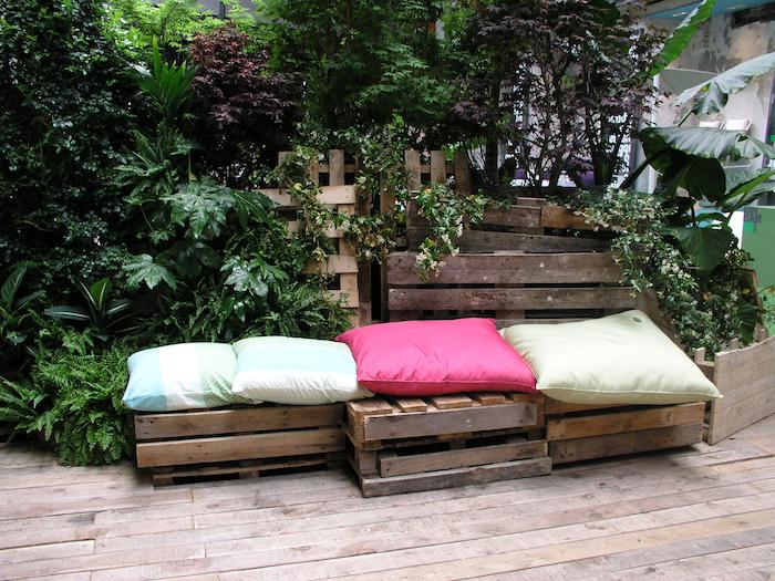 mur végétal extérieur avec une banquette en planches de bois de palette, coussins vert, rose et bleu, terrasse bois