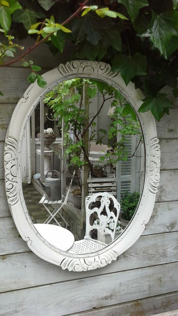 miroir ovale cadre blanc accroché au cintre blanc, meubles de jardin en métal blanc en style baroque, avec des effets de dentelle sur les dossiers, décorer son jardin en style