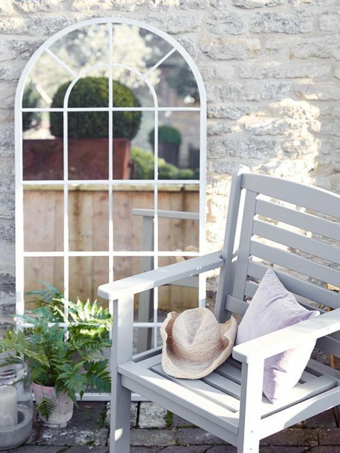 jardin avec élément décoratif grand miroir blanc, jardin deco, decorer son jardin en style minimaliste, chaise en bois blanc avec coussin en rose pastel et chapeau plié en paille