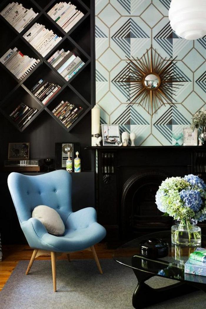 papier peint, tapis mural, habiller un mur de motifs graphiques en vert menthe et noir, étagères casiers en bois noir en forme de losanges avec des livres, fauteuil en tissu bleu pastel avec dossier et surface inférieure en effets matelassés