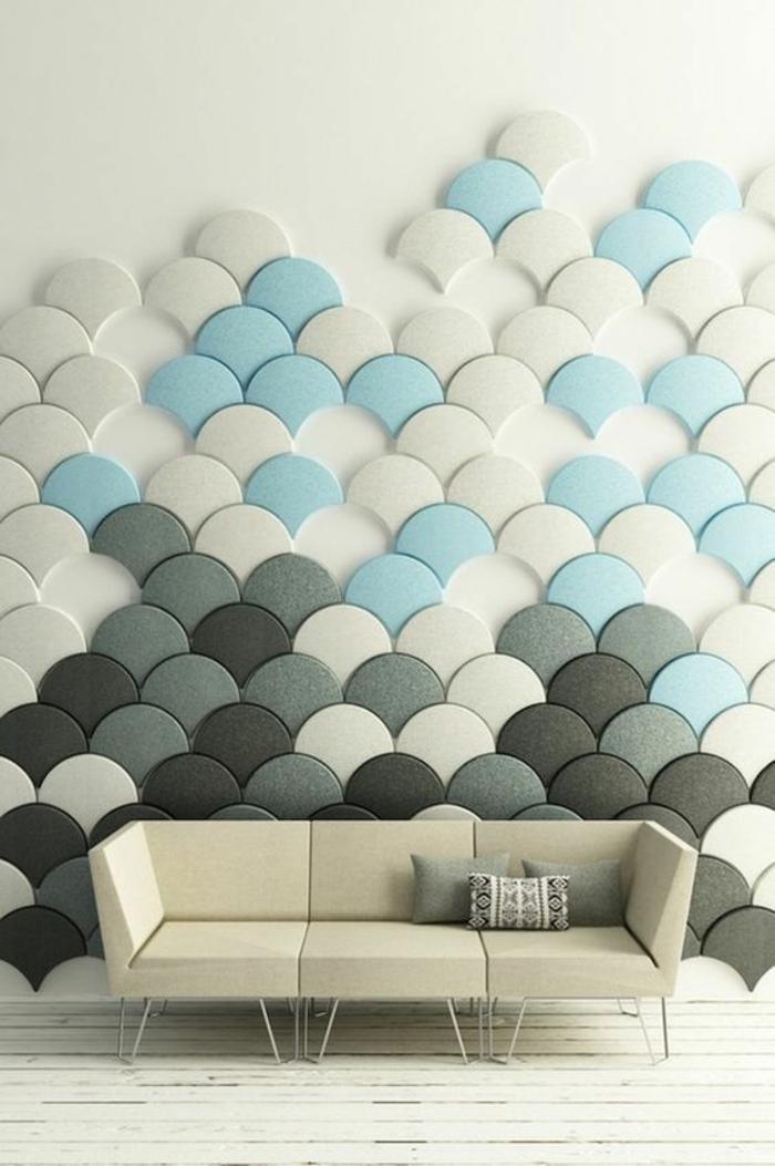 mur décoré avec des mini-panneaux en formes d'écailles de poisson en bleu pastel, gris, blanc et noir, canapé en ivoire aux lignes géométriques minimalistes, decoration murale design, parquet peint en blanc