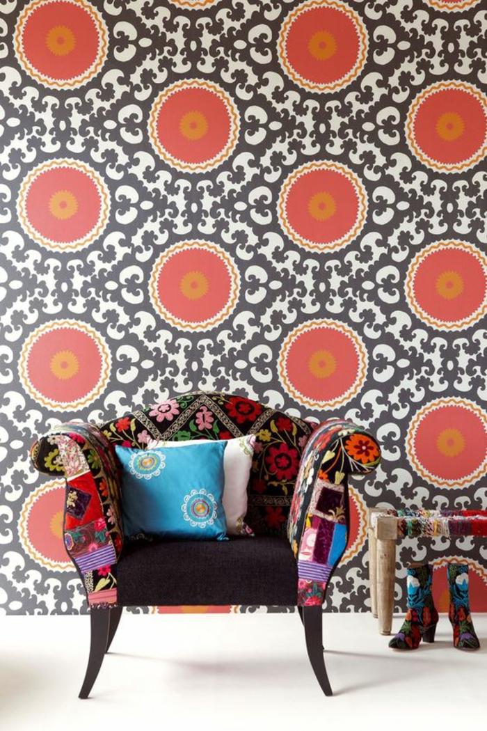 habiller un mur en orange et noir, motifs grands cercles et arabesques, papier peint, fauteuil large au dossier bas, un coussin carré en ivoire, un coussin en turquoise