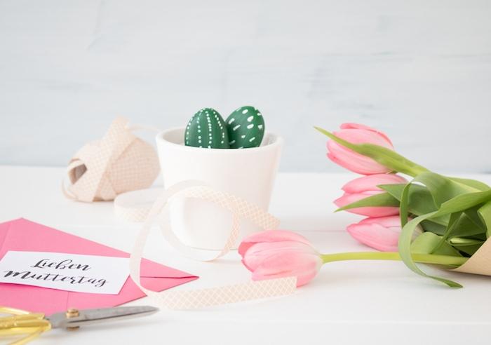 exemple de pot de fleur blanc avec des galets décorés pour imiter des cactus en vert et blanc, activite fete des meres