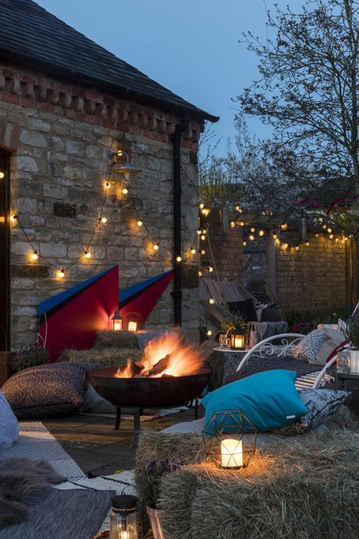 décorer son jardin avec des guirlandes lumineuses, feu central cheminée ronde, coussins multicolores pour s'asseoir, amenagement exterieur