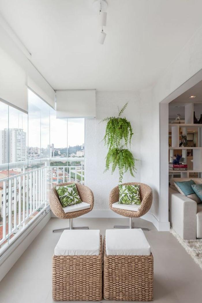 deux fauteuils en couleur beige, deux tabourets en rotin tressé avec des coussins carrés blancs, mur blanc décoré avec deux plantes vertes rampantes, amenagement petite terrasse