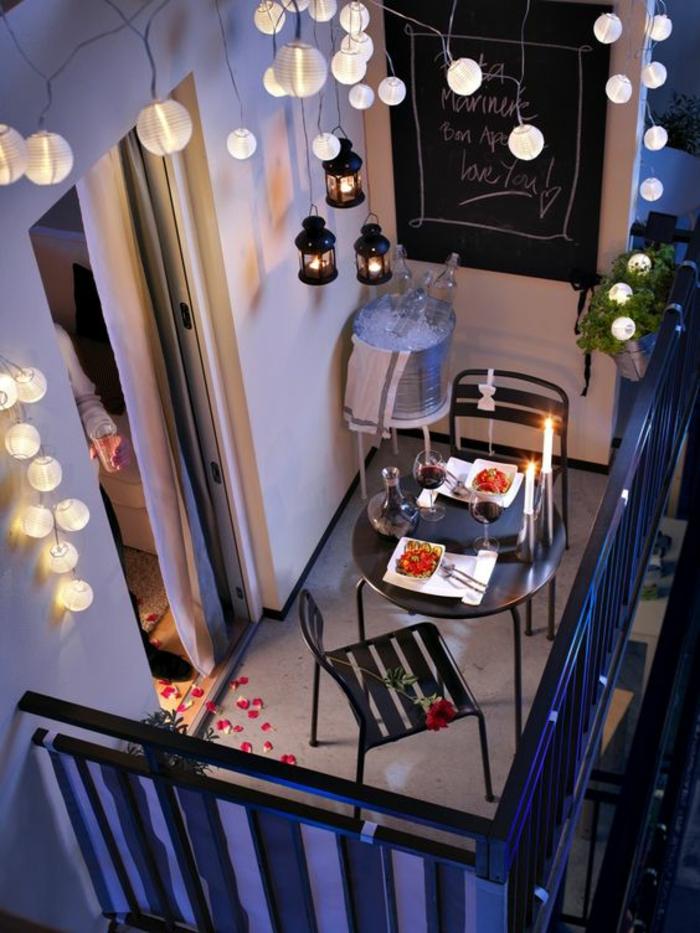 une terrasse du soir illuminée par une guirlande de coules lanternes blanches, decoration terrasse exterieur, sol recouvert de pétales de roses soirée romantique, deux chaises et une table en métal noir, trois lanternes métal noir suspendues au plafond