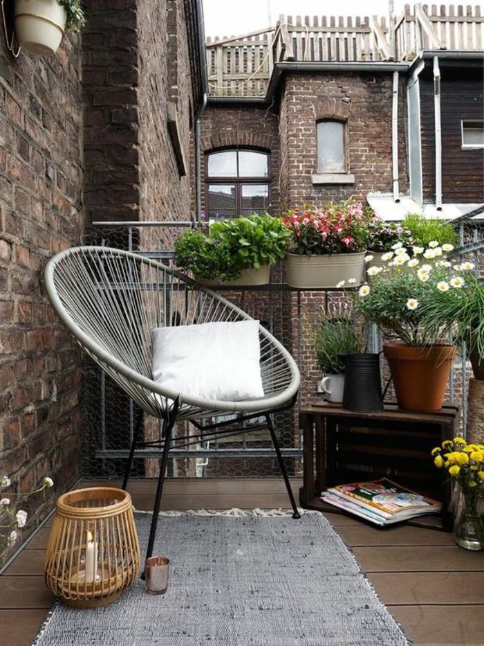 terrasse dans un style bohème, fauteuil rond avec des pieds en métal noir et en fil tressé gris, tapis rectangulaire gris, lanterne en canne avec une bougie blanche dedans, idée déco appartement, pots avec des fleurs