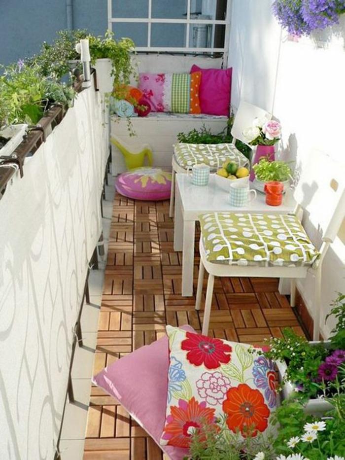 idee amenagemet terrasse en couleurs multiples, grands coussins carrés aux motifs fleuris, sol recouvert de bois avec des motifs de parquet, fauteuil deux places blanc dans l'un des bouts avec des coussins carrés en couleurs