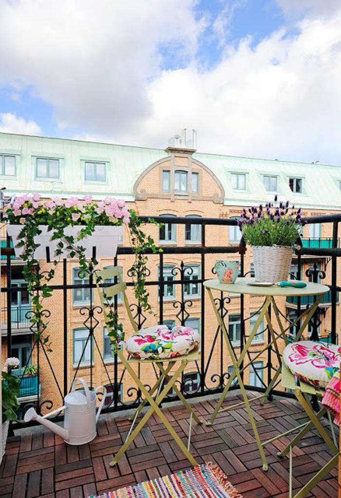 terrasse aménagée en style romantique, idee amenagement terrasse, deux chaises pliables couleur moutarde et table ronde pliable en moutarde, sol recouvert lame bois a emboîter, tapis coloré en style ethnique