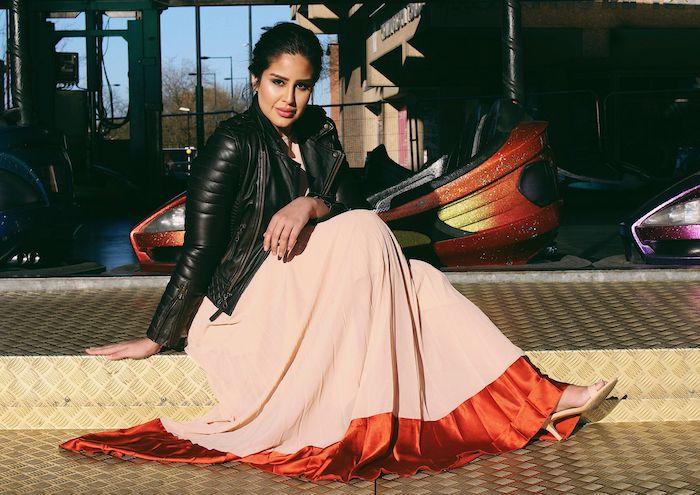 veste en cuir noir et une robe grande taille longue évasée en rose pale et rouge en ourlet, maquillage femme indienne
