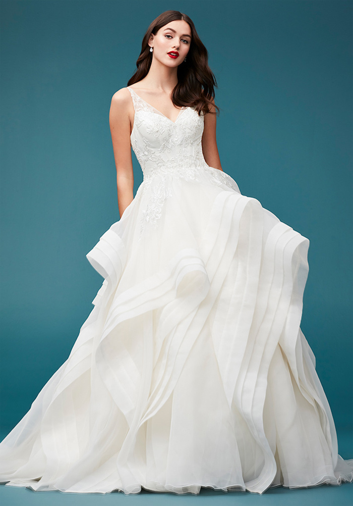 robe de mariée haute couture avec un top décoré de pierres et une jupe en tulle plissée, cheveux lachés