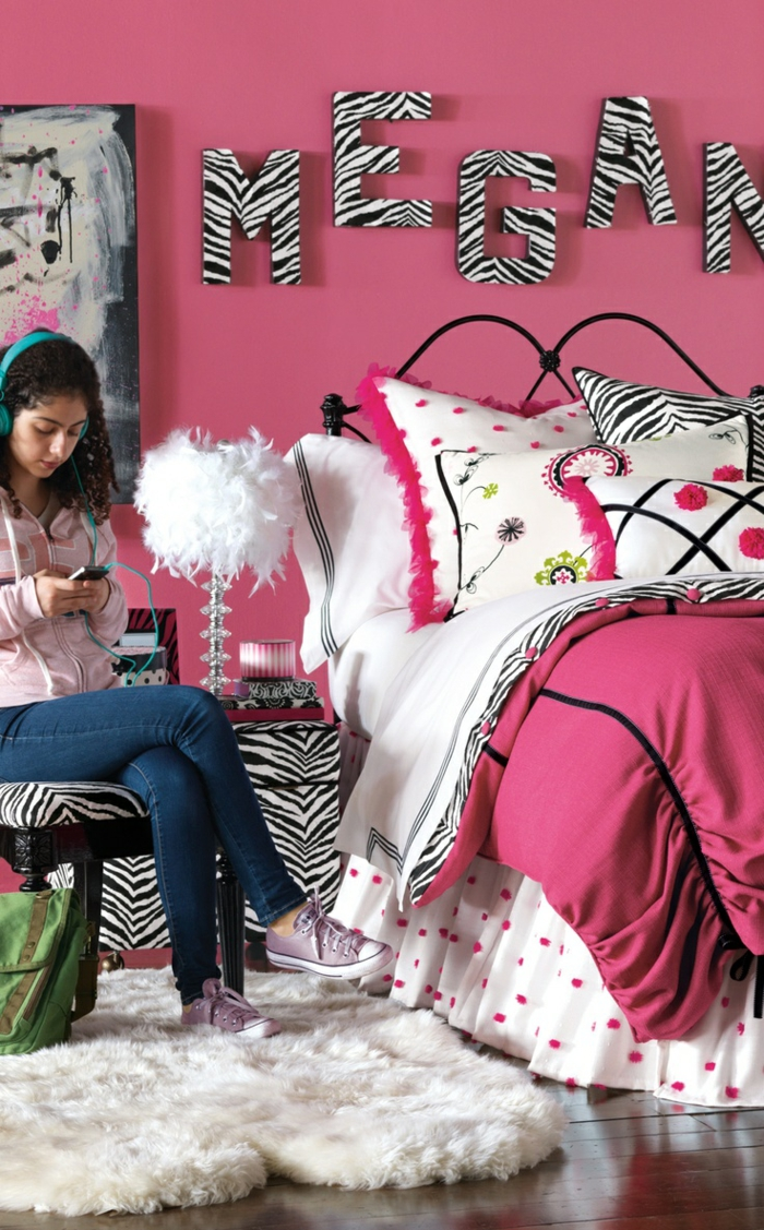 déco chambre fille ado, murs en fuchsia, inscription grande taille avec le nom de la fille au mur aux imprimés zèbre, grand lit, tete de lit en métal noir, tapis pols long blanc