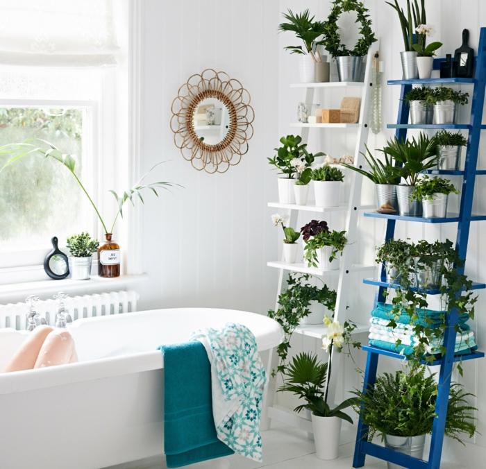 plante interieur ombre, salle de bain verte, échelle blanche et échelle en bleu marine, miroir avec cadre en forme de fleur en osier tressé, baignoire blanche, dalles de carrelage blanches