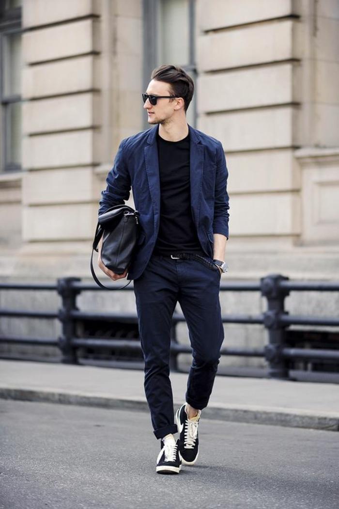 tenue homme chic, pantalon en bleu nuit, veste en bleu nuit, T-shirt noir, baskets noires avec des lacets blancs, grand sac en noir type besace