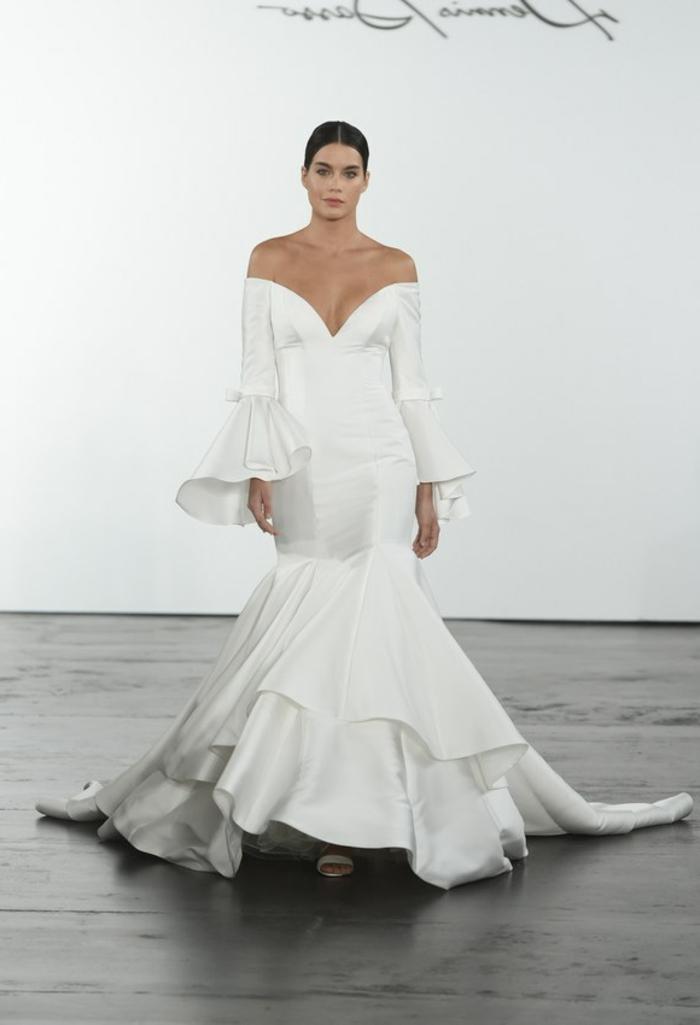 une robe de Dennis Basso, modèle aux manches longues fortement évasée aux bouts, grands volants sur les ourlets de la robe, robe de mariée sirène