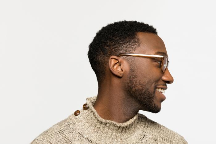 lunettes homme Felix Gray, monture de lunette, plastique marron et branches en métal doré, finition de luxe, homme afro avec pull en grosse laine beige