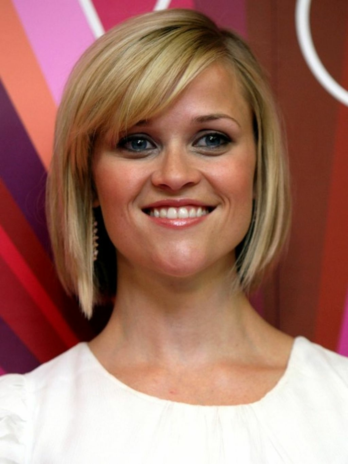 carré court blond de Reese Witherspoon, frange asymétrique, look de femme stricte